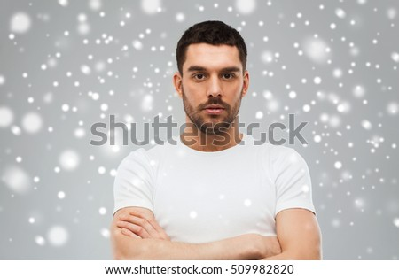 people, winter and christmas concept - young man with crossed arms over snow on gray background