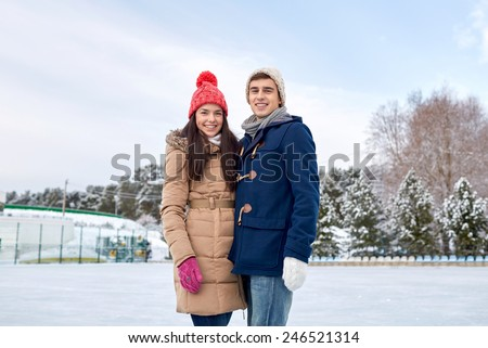 people, winter, friendship, love and leisure concept - happy couple ice skating on rink outdoors - stock photo