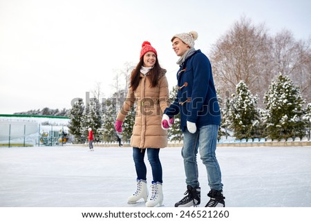 people, winter, friendship, sport and leisure concept - happy couple ice skating on rink outdoors - stock photo