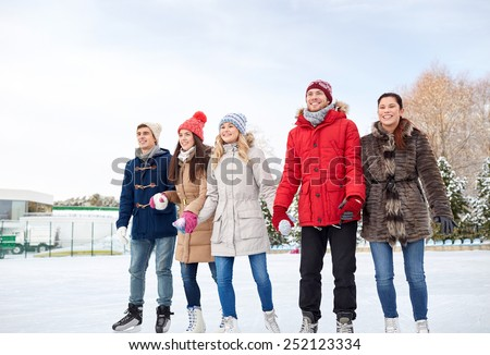 people, winter, friendship, sport and leisure concept - happy friends ice skating on rink outdoors - stock photo