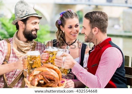 People with beer and pretzel in Bavarian inn eating and drinking - stock photo