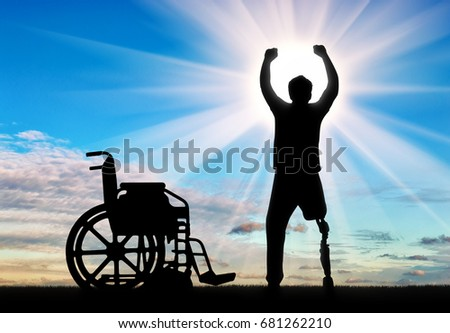 People with disabilities the concept. Happy disabled man with a prosthetic leg standing near a wheelchair at dawn