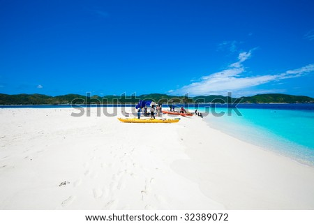 People with kayaks on deserted cay in Japan - stock photo