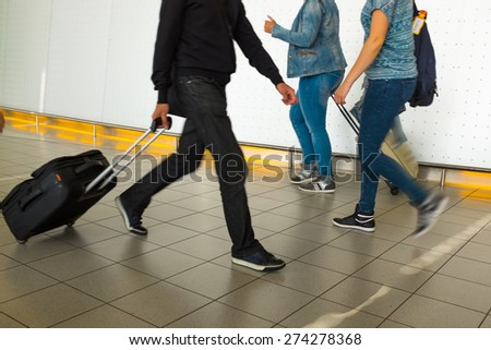 People with luggage walking at the airport. Details. Blurred motion. - stock photo