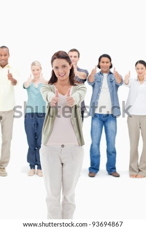 People with their thumbs-up focus on the woman in foreground - stock photo