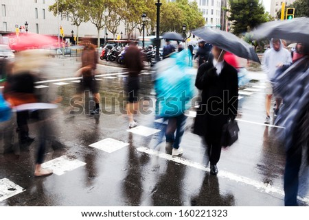 people with umbrellas in motion blur crossing the wet city street