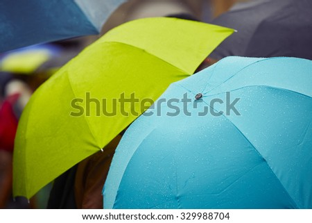 People with umbrellas in rain on the street - selective focus - stock photo