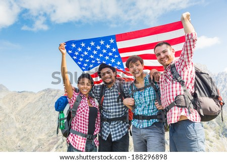 People with USA Flag on top of Mountain - stock photo