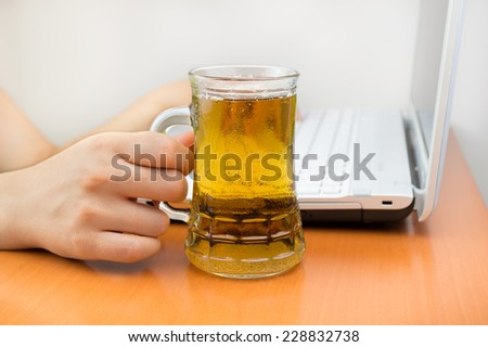 people working at the laptop and drinking a tankard  - stock photo