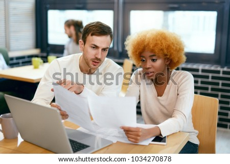 People Working On Notebook In Cafe. Smiling Young Man And Beautiful Black Woman Working Together On Project, Using Computer And Sharing Ideas In Coffee Shop. Business Team At Work. High Quality