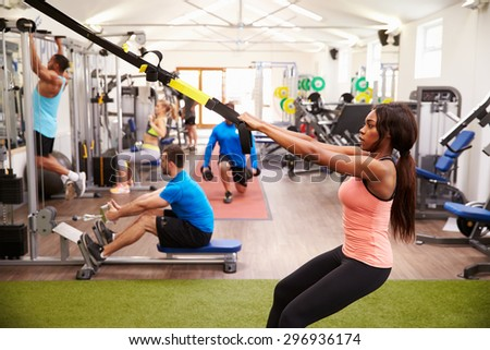 People working out on fitness equipment at a busy gym - stock photo