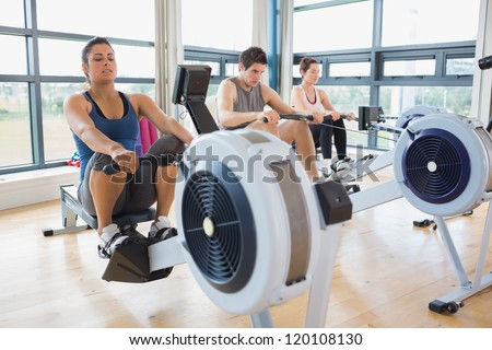 People working out on row machines in fitness studio - stock photo