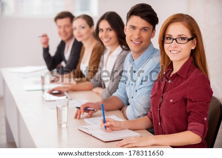 People working together. Group of young people sitting together at the table and smiling at camera - stock photo