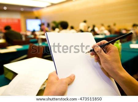 people writing on the document in a business seminar.
