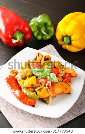Peperonata: peppers cut into slices and baked in a pan with garlic, onion and tomato sauce on complex background