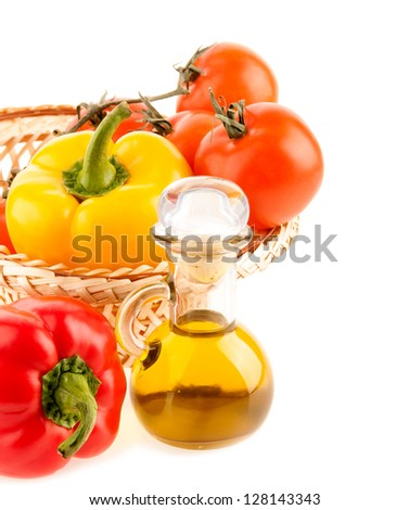 pepper and a bottle with olive oil on the background of the wattled dish with the vegetables on the white