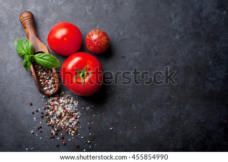 Pepper and salt spices, basil herb and tomatoes. Red, white and black peppercorn. On dark stone table. Top view with copy space