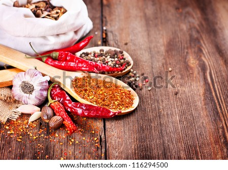 Pepper and spices on wooden background - stock photo