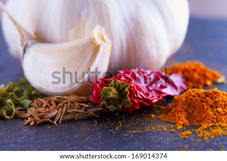 Pepper, garlic, curry and other seasoning over black plate - stock photo