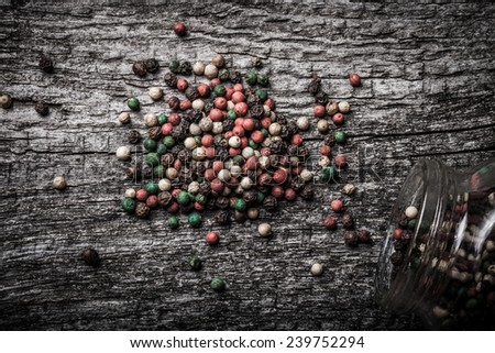 pepper spilled from glass jar on old wooden table - stock photo