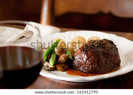 Pepper steak with vegetables and glass of red wine - stock photo