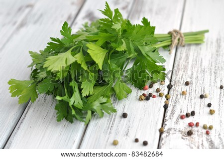 Peppercorn mix and fresh parsley on an old white table - stock photo