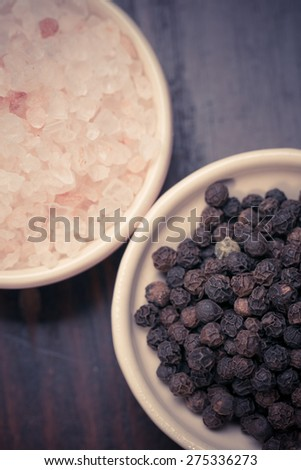 Peppercorns and pink himalayan salt , in small dishes over wooden background