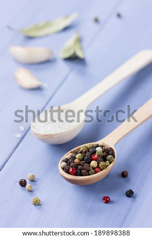 Peppercorns, sea salt in a wooden spoon with garlic and bay leaf on a blue table - stock photo