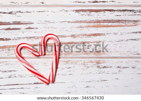Peppermint Candy Canes in Heart Shape on old wooden background. Christmas