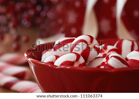Peppermint candy sugar twists in dark red dish with holiday decor, gifts, and candy canes in soft focus in background.  Macro with extremely shallow dof. - stock photo