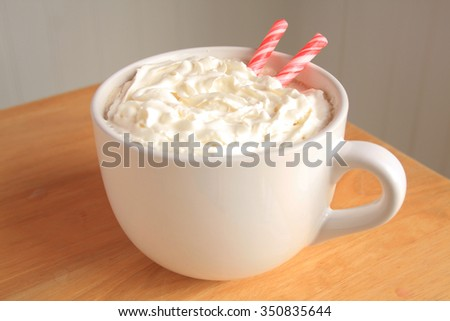 Peppermint coffee or hot coco in a white mug with whipped cream on top with peppermint sticks inside on a wooden table with a white back ground/Peppermint Coffee Sticks/Christmas Sweet - stock photo