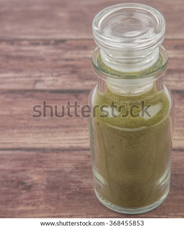 Peppermint herbs powder in glass spice dispenser over wooden background