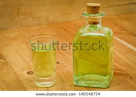 Peppermint liqueur bottle and shot on wooden background - stock photo