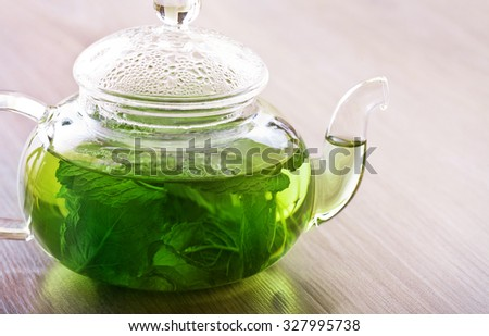 Peppermint tea in a glass pot on the table - stock photo