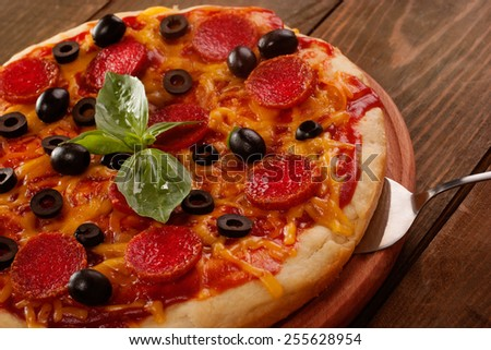 Pepperoni pizza closeup on wooden table - stock photo