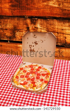 Pepperoni pizza delivery. Tasty pizza with pepperoni sausage in white cardboard box on kitchen table - stock photo