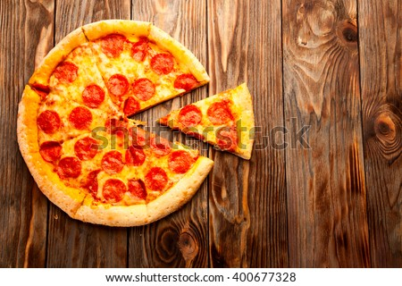 Pepperoni pizza on a wooden table - stock photo