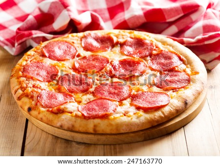 pepperoni pizza on wooden table - stock photo
