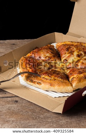 Pepperoni Pizza Ready to Eat in box on wooden background - stock photo