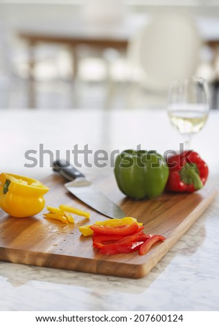 Peppers and knife on chopping board in kitchen - stock photo