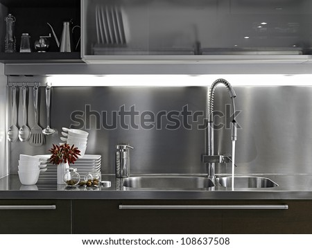 peppers and white dishes on the steel surface in the kitchen