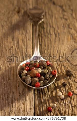 Peppers seeds on spoon over rustic wooden table - stock photo