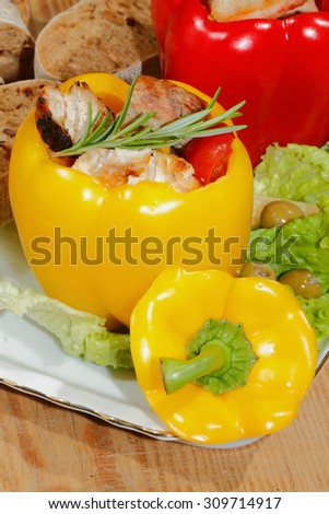Peppers stuffed with grilled turkey breast and stewed tomatoes, zucchini and vegetables garnished with lettuce leaves, corn cobs, olives and rosemary