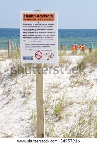 PERDIDO KEY, FL - JUNE 10:  A warning sign is posted at the beach in Perdido Key, FL as the oil washes ashore on June 10, 2010.  Oil spill workers can be seen in the distance. - stock photo
