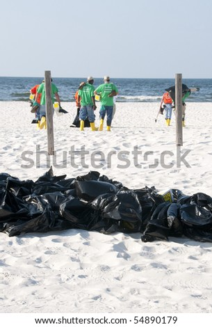 PERDIDO KEY, FL - JUNE 9: Garbage bags filled with potentially tainted seawood lie on the beach as BP oil spill workers clean the beaches on June 9, 2010 in Perdido Key, FL. - stock photo