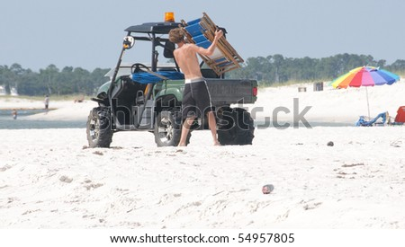 PERDIDO KEY - JUNE 10: A beach chair vendor closes up early on a perfect beach day as oil washes ashore at Perdido Pass, AL on June 10, 2010. - stock photo