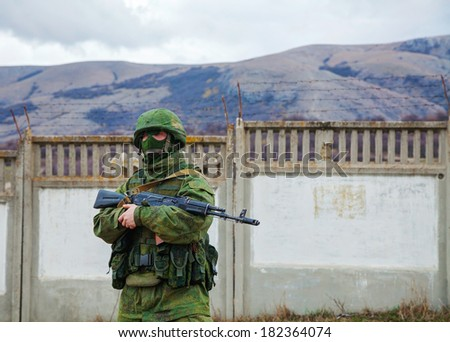 PEREVALNE, UKRAINE - MARCH 5: Russian soldier guarding an Ukrainian naval base on March 5, 2014 in Perevalne, Crimea, Ukraine. On February 28, 2014 Russian military forces invaded Crimea peninsula. - stock photo