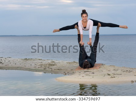 Perfect acro yoga. Beautiful young couple pair is balancing doing acro yoga. Pair yoga concept. Yoga flexibility outdoor class workout. Healthy yoga lifestyle