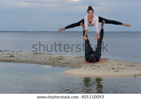 Perfect acroyoga. Beautiful young couple is balancing doing acro-yoga. Pair yoga concept. Yoga flexibility outdoor class workout
