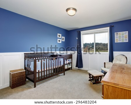 Perfect baby room with beautiful deep blue walls, and stained wood crib. - stock photo